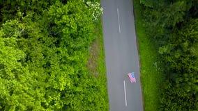 La jeune femme adolescente ondulant un drapeau des USA est patinage de rouleau sur la route rurale Vue à partir du dessus banque de vidéos