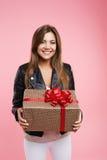 La jeune femme adorable semble heureuse avec la grande boîte actuelle brune Photos libres de droits
