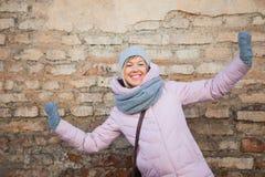 La jeune femme adulte dans des mitaines d'écharpe ont l'amusement sur le vieux mur de briques Image libre de droits