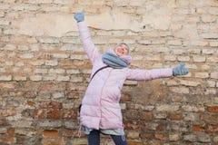 La jeune femme adulte ont l'amusement sur le vieux fond de mur de briques Photo libre de droits