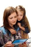 La jeune femme affiche un livre une petite fille. Photos stock