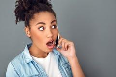 La jeune femme africaine d'isolement sur le mode de vie quotidien occasionnel de studio gris de mur a choqué l'appel téléphonique photo libre de droits