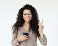 La jeune femme africaine tient le téléphone portable moderne images libres de droits