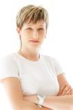 La jeune femme agréable sur un fond blanc sourit Photographie stock