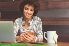 La jeune femme agréable tient le téléphone portable avec le sourire Images libres de droits