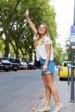La jeune femme appelle un taxi Photos stock