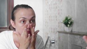 La jeune femme applique la crème sur le visage avec des mouvements de massage à la salle de bains clips vidéos