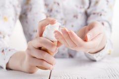 La jeune femme applique la crème sur ses mains Sur un fond blanc photo stock