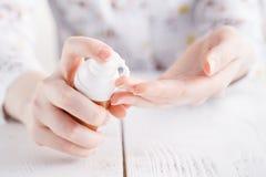 La jeune femme applique la crème sur ses mains Sur un fond blanc photographie stock
