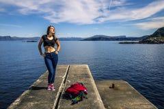 La jeune femme apprécie le jour ensoleillé sur le fjord, Norvège Photographie stock