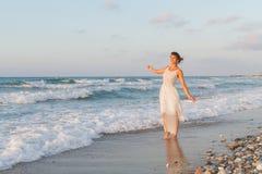 La jeune femme apprécie une promenade seule sur la plage au crépuscule Photos libres de droits