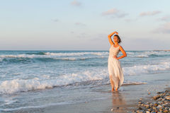 La jeune femme apprécie une promenade seule sur la plage au crépuscule Photographie stock