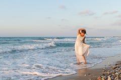 La jeune femme apprécie une promenade seule sur la plage au crépuscule Image stock