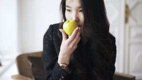 La jeune femme asiatique avec un livre prend une pomme verte et la sent banque de vidéos