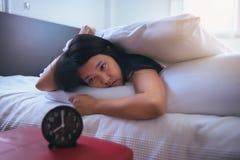 La jeune femme asiatique déteste obtenir se réveiller soumis à une contrainte tôt, femelle étirant sa main à l'alarme de sonnerie photos stock