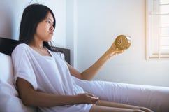 La jeune femme asiatique déteste obtenir se réveiller soumis à une contrainte tôt, femelle étirant sa main à l'alarme de sonnerie image libre de droits