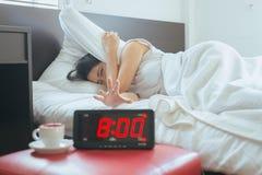 La jeune femme asiatique déteste obtenir soumise à une contrainte réveillant tôt l'horloge de ` de 8 o, réveil image stock