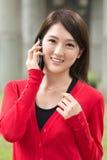 La jeune femme asiatique de sourire prennent un appel photos stock