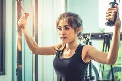 La jeune femme asiatique faisant la corde ?lastique s'exerce au gymnase crois? de forme physique Formation de force et musculaire photo stock