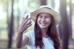 La jeune femme asiatique a mis dessus le chapeau et selfie de prise au téléphone portable photographie stock libre de droits