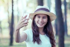 La jeune femme asiatique a mis dessus le chapeau et selfie de prise au téléphone portable image stock