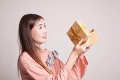 La jeune femme asiatique ouvrent un boîte-cadeau Images stock