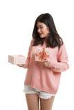 La jeune femme asiatique ouvrent un boîte-cadeau Image stock