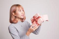 La jeune femme asiatique ouvrent un boîte-cadeau Photo stock