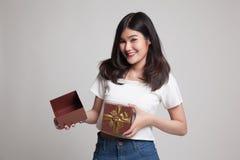 La jeune femme asiatique ouvrent un boîte-cadeau d'or Photographie stock