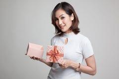 La jeune femme asiatique ouvrent un boîte-cadeau d'or Image stock