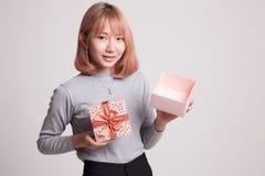 La jeune femme asiatique ouvrent un boîte-cadeau d'or Photo libre de droits