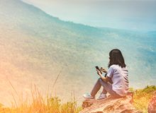 La jeune femme asiatique s'asseyent sur la roche à la falaise et à employer le message téléphonique futé à ses amis tandis que de Image libre de droits