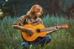 La jeune femme assez caucasienne dans la chemise et des blues-jean de plaid est Photos libres de droits