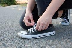 La jeune femme attache des dentelles dans des espadrilles sur la route goudronnée dans la ville en PS Photographie stock libre de droits
