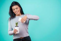 La jeune femme attirante élève la fleur à la maison image stock