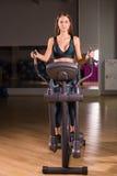 La jeune femme attirante établit sur un entraîneur elliptique dans le gymnase Photos libres de droits