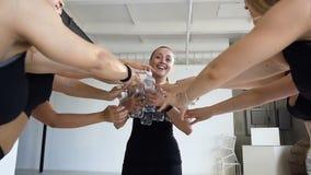 La jeune femme attirante a apporté des bouteilles avec de l'eau pour boire pour des femmes après séance d'entraînement de sport d banque de vidéos