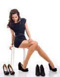 La jeune femme attirante avec de longs cheveux choisit des chaussures photographie stock libre de droits