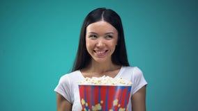 La jeune femme attirante avec la grande tasse de maïs éclaté jetant un coup d'oeil rapidement, flirtent dans le cinéma banque de vidéos