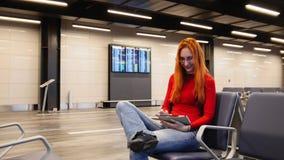 La jeune femme attirante avec les cheveux rouges et les verres utilisent l'instrument dans le salon de départ d'aéroport image stock