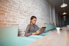 La jeune femme attirante a concentré lire le livre électronique sur son comprimé numérique, Photos stock