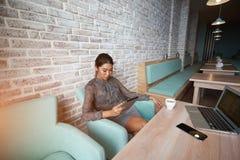 La jeune femme attirante a concentré lire le livre électronique sur son comprimé numérique, Images libres de droits