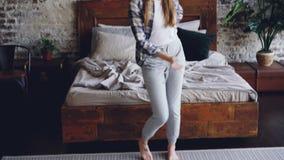 La jeune femme attirante dans des vêtements sport danse sur le plancher de chambre à coucher et écoute la musique dans des écoute clips vidéos