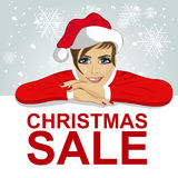 La jeune femme attirante dans le chapeau de Santa s'est appuyée sur le conseil vide avec le texte rouge de vente de Noël Images libres de droits