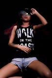 La jeune femme attirante dans le chapeau et des lunettes de soleil, fume sur un fond foncé Soyez à la mode, soyez frappeur Image libre de droits