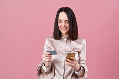 La jeune femme attirante de brune dans un chemisier élégant fait les achats en ligne et emploie un téléphone et une carte de banq photographie stock libre de droits