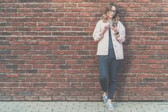 La jeune femme attirante de hippie en verres se tient dehors sur le fond rouge de mur de briques, regardant l'écran du téléphone, Photo stock