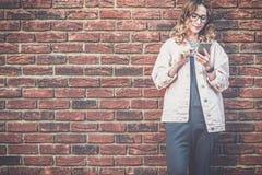La jeune femme attirante de hippie en verres se tient dehors sur le fond rouge de mur de briques, regardant l'écran du téléphone, Photos stock