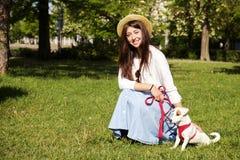 La jeune femme attirante de hippie a fait une promenade en parc, jouant avec le chiot mignon de terrier de Russell de cric le jou Photos libres de droits