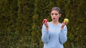 La jeune femme attirante de portrait dans la veste bleue choisit entre la pomme verte et la pomme rouge banque de vidéos